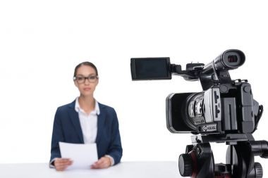 Attractive female newscaster with papers sitting in front of camera, isolated on white stock vector