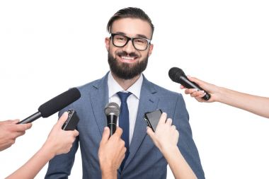 journalists with microphones interviewing businessman