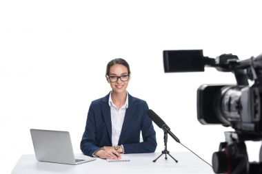 newscaster with laptop looking at camera