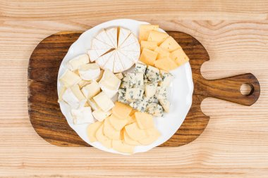 variety of cheese kinds on wooden board