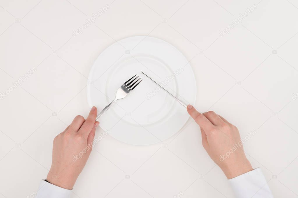 hands, empty plate and cutlery