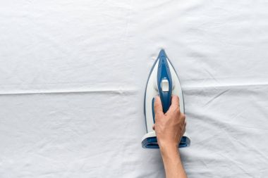 man ironing bed sheets