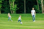 Photo father with kids playing soccer in park