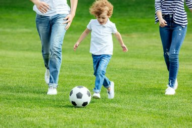 family with soccer ball in park