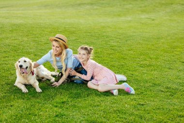 Mother and daughter with dog at park