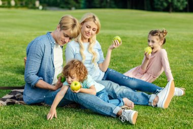 family eating apples in park