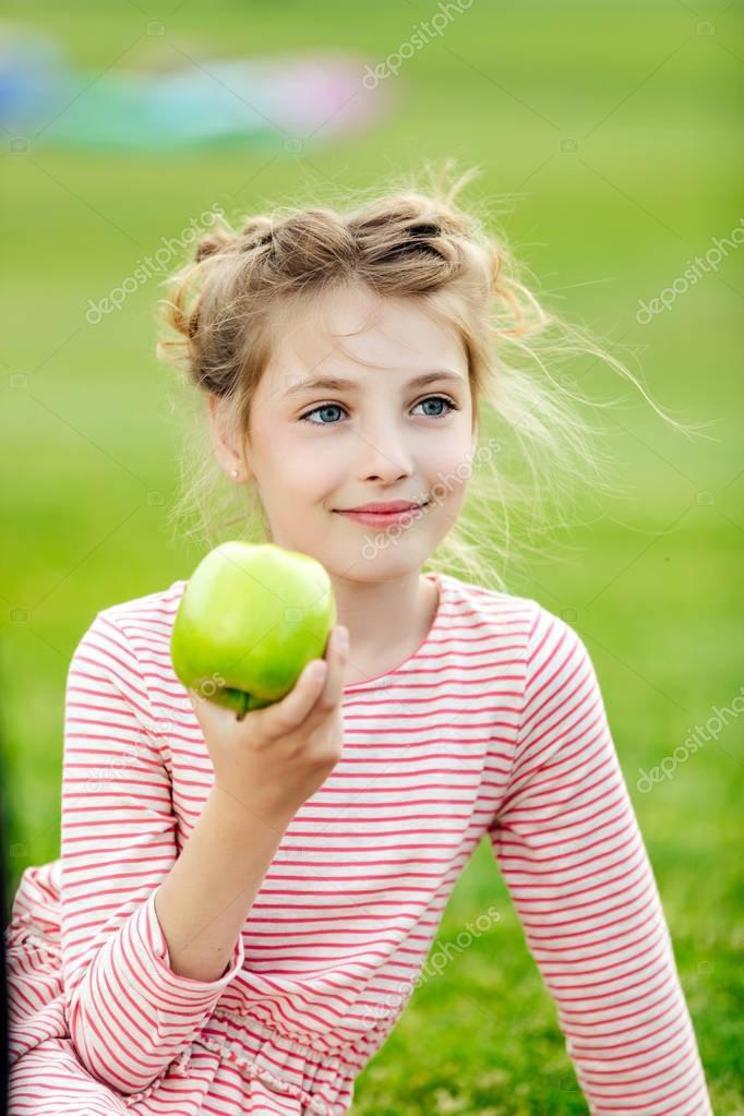 girl eating apple in park