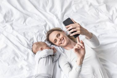 Mother taking selfie with baby