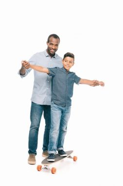 African american father and son with skateboard