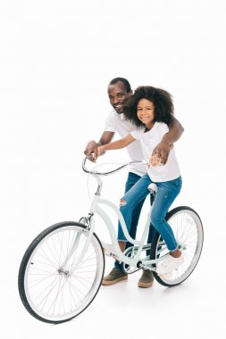 Father teaching daughter riding bicycle