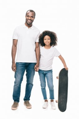 Happy father and daughter with skateboard