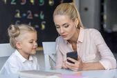Fényképek Anya és lánya használ smartphone