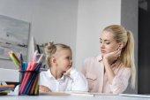 Fotografie mother and daughter doing homework