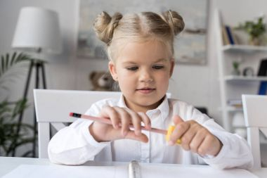 child sharpening pencil