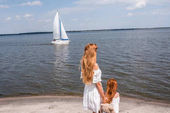 Fotografie mother and daughter looking at yacht