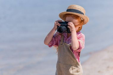 Cute little redhead girl photographing with camera at seashore stock vector