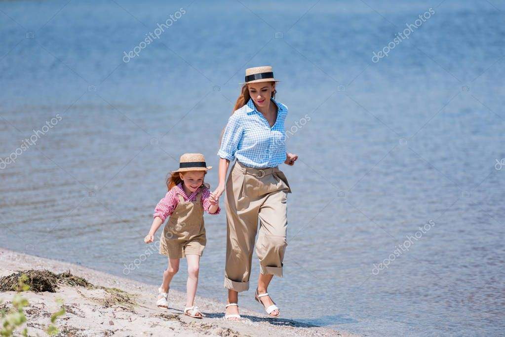 mother and daughter walking at seashore