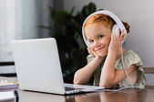 Fotografie kleines Mädchen mit Kopfhörern und laptop