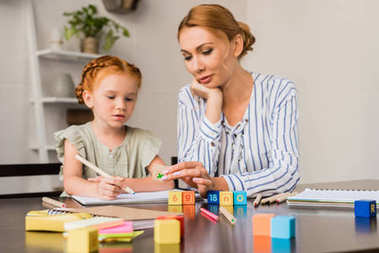 mother and daughter learning math with cubes