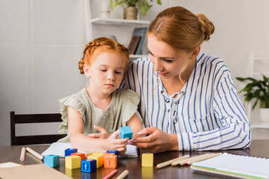 Mother and daughter learning with letter cubes