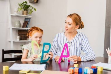 mother and daughter learning alphabet