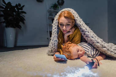 daughter sleeping white mother using smartphone