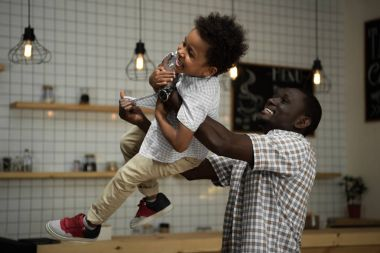 African american father carrying son