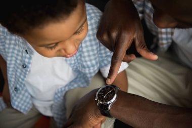 Father and son checking wristwatch