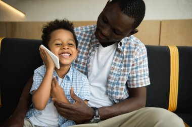 african american father and son with smartphone