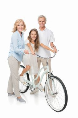 Girl on bicycle with grandparents