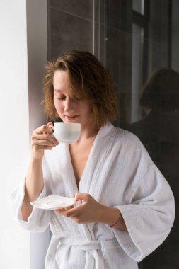 Girl in bathrobe drinking coffee