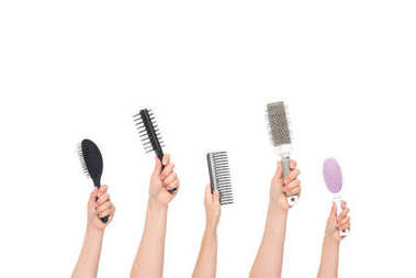 hands holding hairbrushes