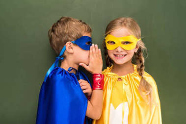 Little pupils in superhero costumes gossiping with chalkboard behind stock vector