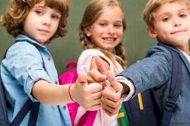 schoolchildren showing thumbs up