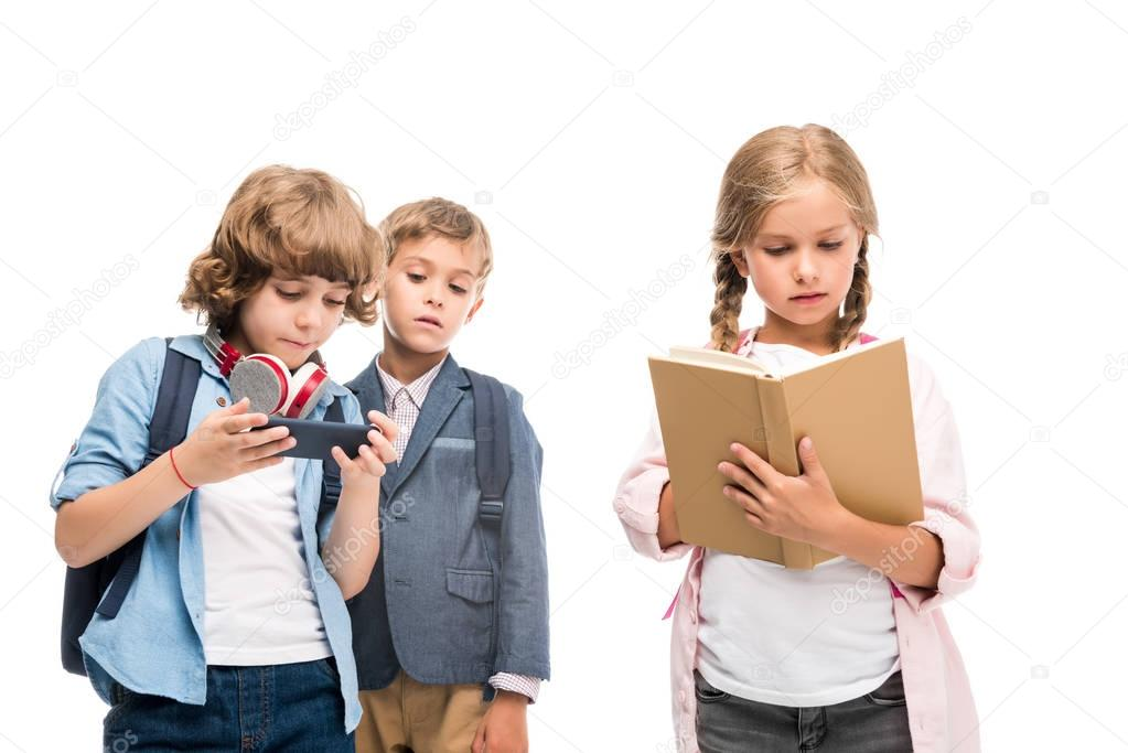 schoolboys with smartphone and schoolgirl with book