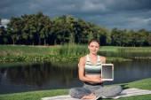 Fotografie ženy cvičení jógy s tabletem