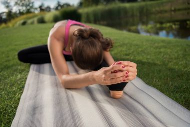 woman practicing yoga on mat