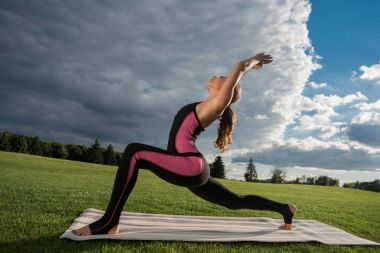 woman performing yoga at countryside