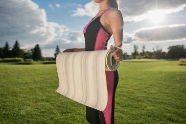 woman in sportswear holding yoga mat