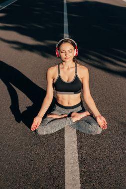woman in lotus pose listening music