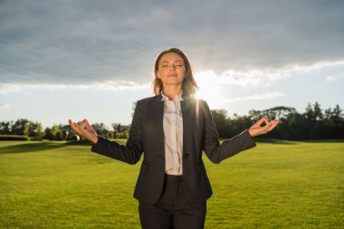 smiling businesswoman meditating in park