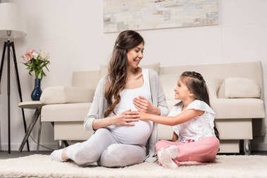 Pregnant woman with daughter touching belly