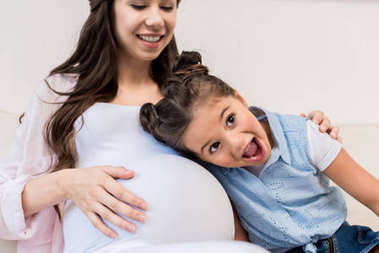 Girl listening to belly of pregnant mother