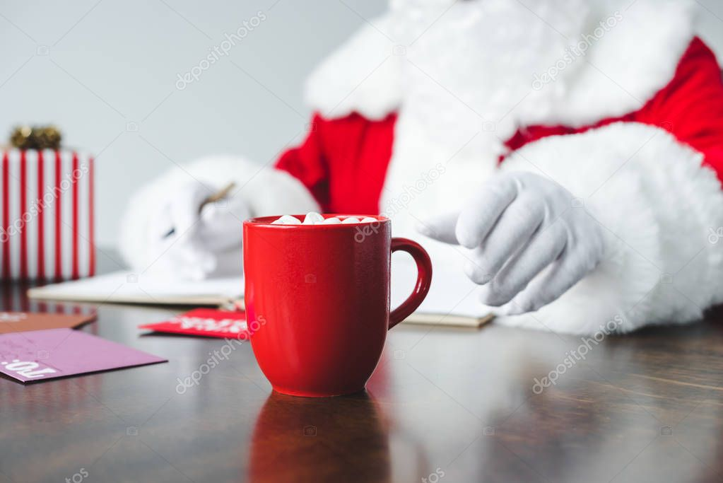 santa drinking hot chocolate with marshmallows