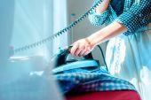 Fotografie Žena v domácnosti, žehlení a mluví o telefonu