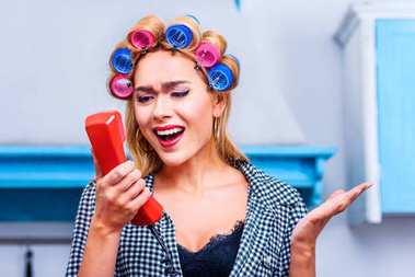 Angry housewife in curlers talking on vintage telephone stock vector