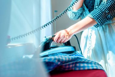 housewife ironing and talking on telephone