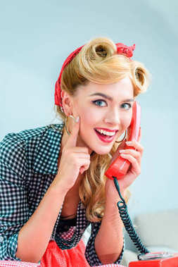 Beautiful smiling pin up girl talking on vintage telephone stock vector