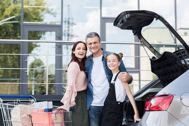 family with shopping cart next to car