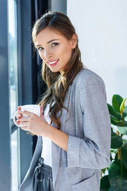 Beautiful young businesswoman holding cup and smiling at camera stock vector